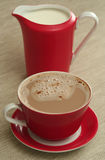 La cuvette du café et le lait sont sur une table Photo stock
