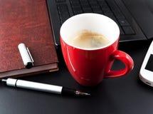 La cuvette du café et des affaires objecte sur la table Photos stock