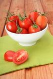 La cuvette a rempli de tomates-cerises sur la serviette verte Photos libres de droits