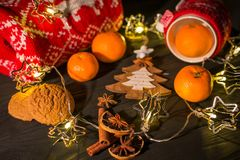 La décoration de Noël avec la bougie et la guirlande s'allume sur le fond rustique rouge Image stock