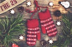 La décoration de Noël avec le rouge a tricoté des mitaines, des brindilles de pin et des jouets de Noël Images stock