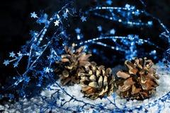 La décoration de Noël avec les étoiles bleues de scintillement filètent le cône d'environ trois pins sur la glace sur le fond noi Photos stock