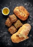La défaite fraîchement cuite au four, le pain de ciabatta et les petits pains de sandwich ont servi avec l'huile d'olive vierge s Photographie stock libre de droits
