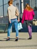 La défense de La, France 10 avril 2014 : vue arrière de deux travailleurs occasionnels marchant sur une rue On porte les pompes e Photos stock