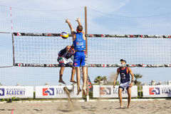 La défense de volleyball de plage d'homme d'athlète Mur sur le filet Bras vers le haut photo stock