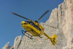 La délivrance médicale de vol d'hélicoptère de délivrance a blessé le grimpeur sur Tre Cime l'Italie, dolomites Photographie stock libre de droits