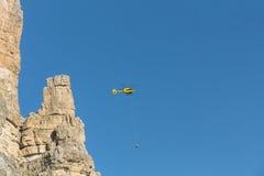 La délivrance médicale de vol d'hélicoptère de délivrance a blessé le grimpeur sur Tre Cime l'Italie, dolomites Images stock
