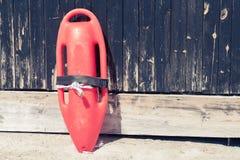 La délivrance peut sur le mur en bois à la plage Photographie stock