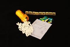 La dépendance a défini avec les pilules blanches renversées ci-dessus de tuiles au-dessus d'un fond de noir de protection de pres photos stock