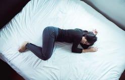 La dépression asiatique de femme ont une tristesse de mal de tête et de sentiment dans la chambre à coucher photos stock