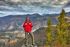 La détente de voyageur de jeune homme extérieure avec les montagnes rocheuses l'automne de fond vacations et mode de vie photos stock
