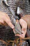 La 2da mitad del guerrero normando del siglo XI afila el cuchillo Foto de archivo libre de regalías