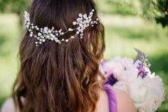 La dama de honor con las peonías coloridas del ramo de la boda y otras flores con la tiara profesional del maquillaje y de la cor foto de archivo