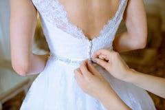 La dama de honor está atando el vestido de boda blanco para la novia hermosa Foto de archivo libre de regalías