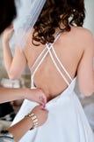 La dama de honor está atando el vestido de boda blanco para la novia hermosa Imagen de archivo libre de regalías