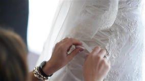 La dama de honor está atando el vestido de boda blanco para la novia hermosa, preparando la boda
