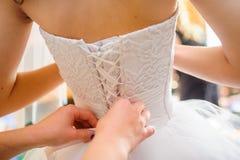 La dama de honor está ayudando a la novia a vestirse Foto de archivo