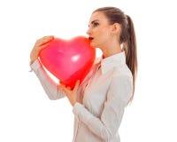La dame élégante avec du charme de brune célèbrent le jour de valentines de saint avec le coeur rouge d'isolement sur le fond bla Image libre de droits