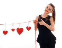 La dame élégante heureuse de brune célèbrent le jour de valentines de saint avec le coeur rouge d'isolement sur le fond blanc Photos stock