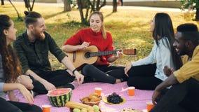 La dame assez jeune joue la guitare tandis que ses amis sont chantants et écoutants la musique se reposant sur le plaid en parc N banque de vidéos