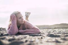 La dame attirante fixent ? la plage sur le sable dans la saison d'hiver ou d'automne avec un chandail rose appr?ciant l'ext?rieur images stock