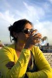 La dame avec du charme en jaune boit du vin du verre Image libre de droits