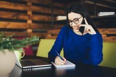 La dame d'affaires parlent du téléphone et font des notes à la table de travail Photos libres de droits