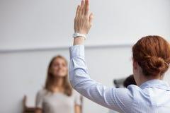 La dame d'affaires soulèvent la main votant au cours de la réunion d'affaires image stock