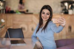 La dame de brune font un selfie en café Madame #37 d'affaires photographie stock libre de droits
