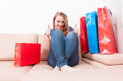 La dame de Shopaholic s'asseyant sur le divan montrant le double aiment Photographie stock libre de droits