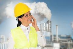 La dame de sourire machinent parler sur le téléphone et l'usine en Th Photo libre de droits