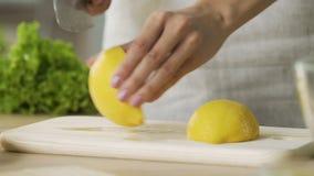 La dame en gros plan remet couper les citrons jaunes, faisant la limonade fraîche, faisant cuire banque de vidéos