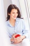 La dame enceinte gaie détend près de la fenêtre Image stock