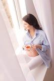 La dame enceinte mignonne apprécie la boisson chaude Photo stock