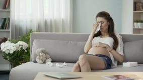 La dame enceinte s'asseyant sur le séchage pleurant de sofa déchire avec le tissu, désordre hormonal banque de vidéos