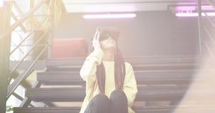 La dame enthousiaste d'Africain découvrent les verres de réalité virtuelle elle s'asseyant sur les escaliers et portant commencer banque de vidéos
