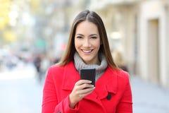 La dame heureuse dans la rue vous regarde tenant le téléphone photographie stock