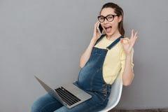 La dame heureuse enceinte parlant par le téléphone font le geste correct Images libres de droits