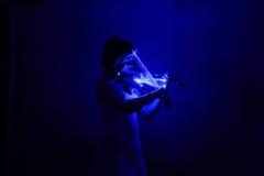 La dame jouant la musique dans l'obscurité Image libre de droits