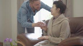 La dame mûre s'asseyant sur le fauteuil en cuir à la maison, elle est malade Le petit-fils adulte apporte le verre de l'eau et do banque de vidéos