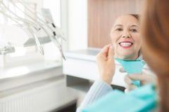 La dame mûre gaie vérifie le travail de l'orthodontiste images stock