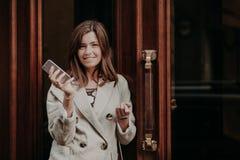 La dame magnifique élégante dans l'imperméable, prises le téléphone portable, attentes l'appel, portes proches extérieures de pos images stock