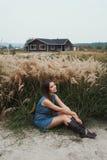 La dame mignonne de campagne repose l'herbe grande de n contre le ranch Photographie stock