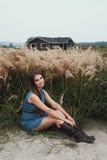 La dame mignonne de campagne repose l'herbe grande de n contre le ranch Photo stock