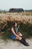 La dame mignonne de campagne repose l'herbe grande de n contre le ranch Photo libre de droits