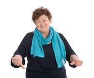 La dame plus âgée d'isolement drôle dans le bleu faisant des pouces font des gestes vers le bas Images libres de droits