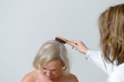 La dame pluse âgé obtient lui des cheveux peignés Photos stock