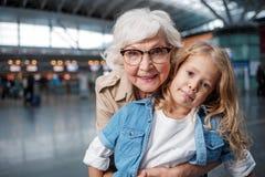 La dame pluse âgé optimiste pose sur le terminal avec la petite fille Images libres de droits