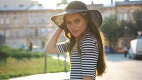 La dame renversante avec de longs cheveux et chapeau noir marche le long de la rue sur le coucher du soleil banque de vidéos