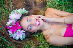 La dame sensuelle en guirlande et perfectionnent le sourire sur l'herbe Image libre de droits